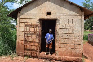 The Water Project: Kavyuni Salvation Army Primary School -  Boy Stands In Front Of Latrine Block