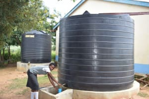 The Water Project: Kaketi Secondary School -  Student Fetching Water From Small Tank