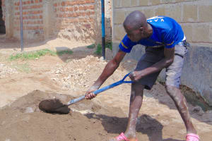 The Water Project: Kosiage Primary School -  Student Helps Mix Cement