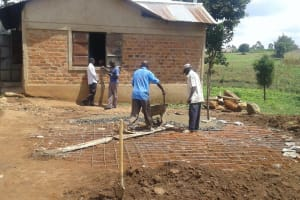 The Water Project: Kamimei Secondary School -  Pouring Concrete Over Tank Stone Foundation