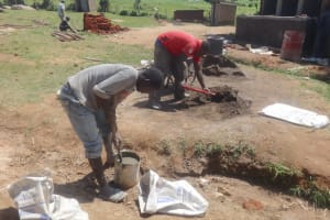 The Water Project: Mwichina Primary School -  Mixing Materials As Latrine Corner Begins In Background