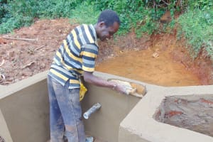 The Water Project: Jivovoli Community, Magumba Spring -  Artisan Smiles While Plastering