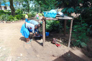 The Water Project: Shikomoli Primary School -  Students Help Wash Utensils At Dishrack