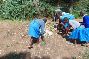 The Water Project: Shikomoli Primary School -  Students Sweep Garbage Into Compost Pit