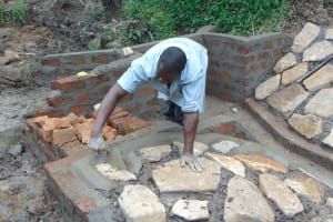 The Water Project: Buyangu Community, Mukhola Spring -  Cementing Stone Pitching