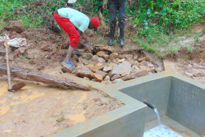 The Water Project: Kimarani Community, Kipsiro Spring -  Backfilling With Large Stones