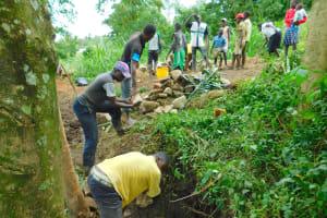The Water Project: Imbinga Community, Imbinga Spring -  Community Members Pass Stones For Backfilling