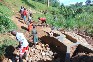 The Water Project: Jivovoli Community, Magumba Spring -  Community Helps Backfill With Stones