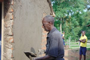 The Water Project: Kosiage Primary School -  Artisan Cements Latrine Walls As Student Looks On