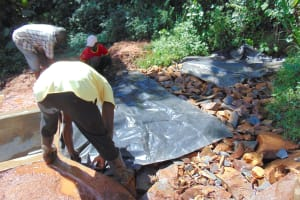 The Water Project: Jivovoli Community, Magumba Spring -  Laying Tarp Over Stones