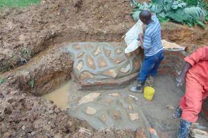 The Water Project: Bumira Community, Imbwaga Spring -  Plastering The Rub Walls