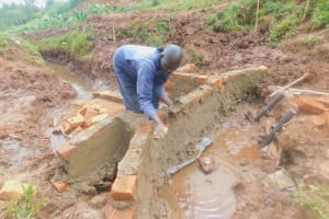The Water Project: Busichula Community, Marko Spring -  Cementing Bricks Of Headwall Into Place
