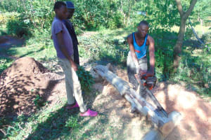 The Water Project: Kipchorwa Primary School -  Cutting Logs For Latrine Foundation
