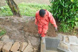 The Water Project: Imbinga Community, Imbinga Spring -  Adding Clay To Backfilling