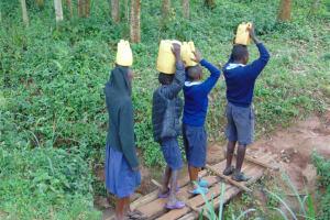 The Water Project: Kabinjari Primary School -  Students Cross The Bridge Carrying Water