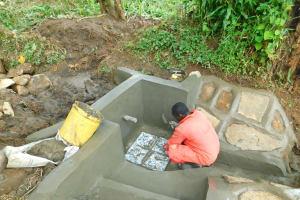 The Water Project: Imbinga Community, Imbinga Spring -  Tile Setting