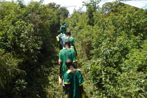 The Water Project: St. Peters Bwanga Primary School -  Students Pass Through Narrow Paths To The Spring