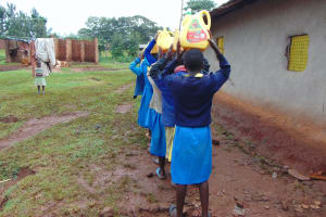 The Water Project: Kitagwa Primary School -  Students Carrying Water To School