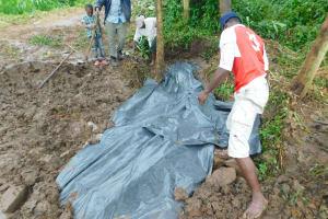 The Water Project: Imbinga Community, Imbinga Spring -  Adding Tarp To Backfilling