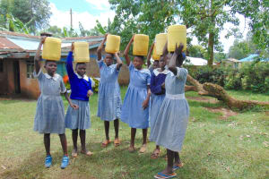 The Water Project: Saosi Primary School -  Students Carrying Water Back To School