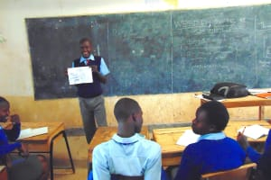 The Water Project: Banja Secondary School -  Student Holds Illustrative Poster