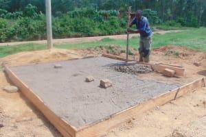 The Water Project: Kipchorwa Primary School -  Pouring Concrete Latrine Foundation