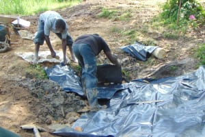 The Water Project: Buyangu Community, Mukhola Spring -  Adding Tarp Over Backfill