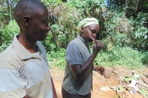 The Water Project: Kisasi Community, Edward Sabwa Spring -  A Woman Demonstrates Toothbrushing Next To Trainer Amos Misiko
