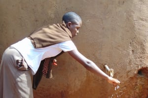 The Water Project: Kitagwa Secondary School -  Student Draws Water From The Small Tank