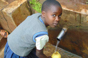 The Water Project: Kapsegeli KAG Primary School -  Student Fetching Water At The Spring