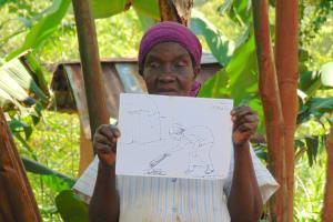 The Water Project: Kimarani Community, Kipsiro Spring -  Woman Holding Training Materials