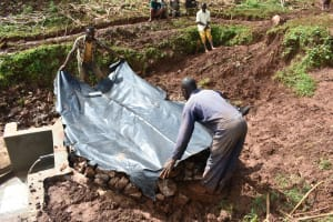 The Water Project: Busichula Community, Marko Spring -  Covering Backfilled Stones With Tarp