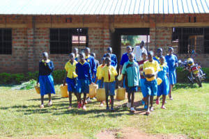 The Water Project: Gimomoi Primary School -  Students Carrying Water