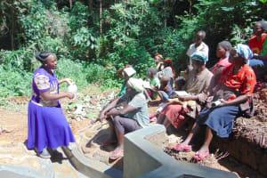 The Water Project: Kisasi Community, Edward Sabwa Spring -  Trainer Karen Maruti Explains How To Use A Leaky Tin For Handwashing