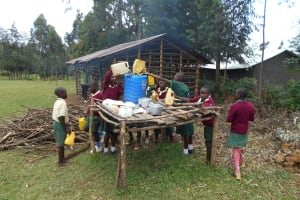 The Water Project: Wavoka Primary School -  Students Pour Water Into A Storage Container