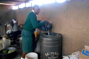 The Water Project: Friends School Manguliro Secondary -  Student Pours Water Into Kitchen Storage Drum