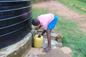The Water Project: St. Joakim Buyangu Primary School -  Pupil Fetching Water