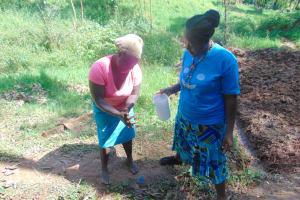 The Water Project: Bumira Community, Imbwaga Spring -  A Volunteer Demonstrates Handwashing