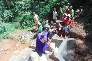 The Water Project: Kisasi Community, Edward Sabwa Spring -  Karen Demonstrates Cleaning A Container With Leaves