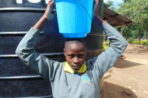 The Water Project: Shikomoli Primary School -  Student Carrying Water