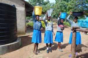 The Water Project: Shikomoli Primary School -  Students Carrying Water