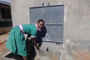 The Water Project: Mwichina Primary School -  Student Enjoying The Rain Tank Water