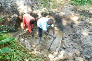 The Water Project: Imbinga Community, Imbinga Spring -  Adding Concrete To Foundation