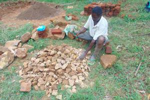 The Water Project: Bumira Community, Imbwaga Spring -  Community Member Breaks Rocks Into Gravel