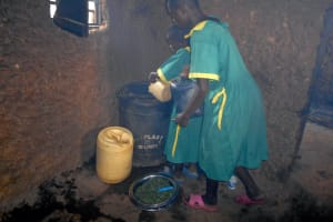 The Water Project: St. Peters Bwanga Primary School -  Students Pour Collected Water Into Kitchen Storage Drum