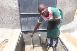 The Water Project: Mwichina Primary School -  Student At The Rain Tank
