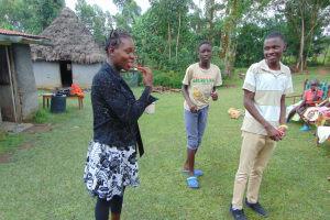 The Water Project: Buyangu Community, Mukhola Spring -  Volunteer Demonstrates Toothbrushing