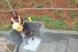 The Water Project: Bumira Community, Imbwaga Spring -  Spring Landowner Stellah Khalawa Washes Her Container Before Fetching Water
