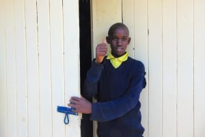 The Water Project: Kosiage Primary School -  Boy Stands In Front Of New Latrine Doors