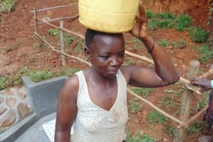 The Water Project: Bumira Community, Imbwaga Spring -  Water Committee Chair Stellah Heads Home With Clean Water
